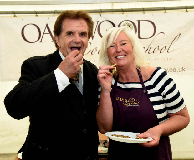 Donnie Munro, the Chieftain in 2016, has a taster at the Tattie Scone Competition with Elaine Sutherland, of the Oakwood Cookery School. Picture - Phil Downie